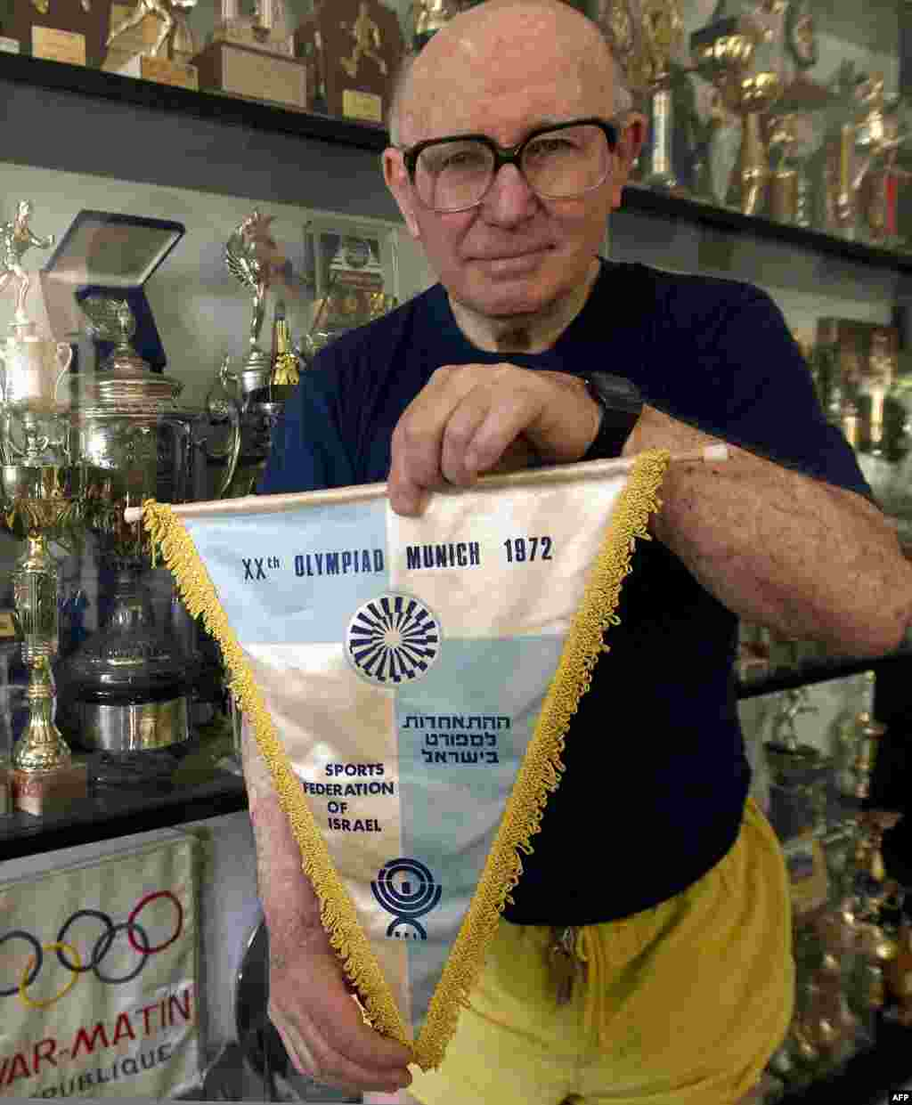 Race walker Shaul Ladany, who escaped a Nazi concentration camp and survived the 1972 Munich ordeal, shows the 1972 Israeli Olympic team's flag at his home in Omer in April 2012.