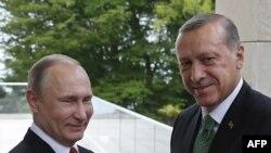 """Президент России Владимир Путин приветствует президента Турции Реджепа Эрдогана в резиденции """"Бочаров ручей""""."""