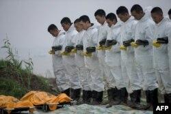 امدادگران در حال ادای احترام به جسد یکی از قربانیان