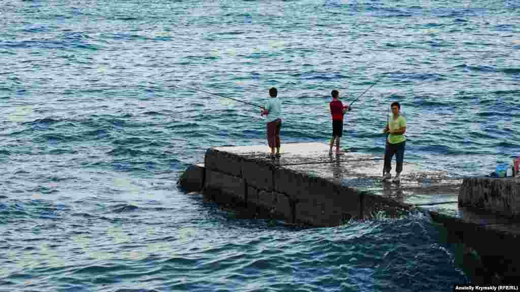 Местные рыбаки не спешат покидать пирс с наступлением сумерек