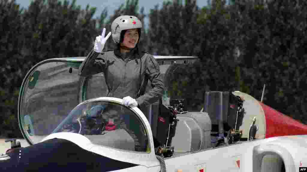 A member of China's first batch of female fighter pilots gestures from her aircraft in August 2009, when authorities said they were recruiting taikonauts from that elite group.