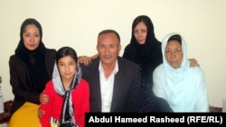 Mohammad Kabir Anwari, and his wife, Rabia (right), pose with three of their six daughters at their home in western Kabul.