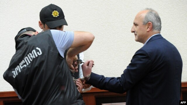 Former Georgian Prime Minister Vano Merabishvili (right) attends a preliminary hearing in his case in Kutaisi on May 22.