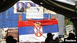 People sit in the tent on a road blockade decorated with the Serbian flag and pictures of Russian Prime Minister Vladimir Putin in the village of Rudare, near Mitrovica on August 7, 2011.