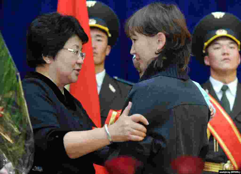 Роза Отунбаева вручает государственную награду супруге погибшего во время июньских событий офицера - Эльвире Абдуллаевой.