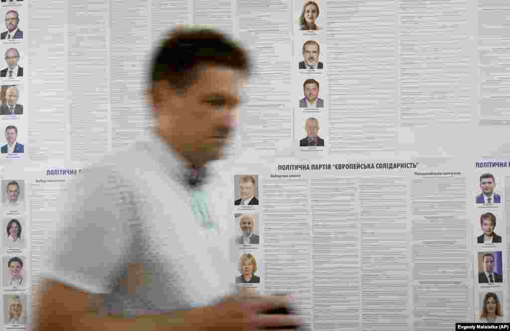A man walks past an election poster with portraits of candidates at a polling station in Kyiv. (AP/Evgeniy Maloletka)