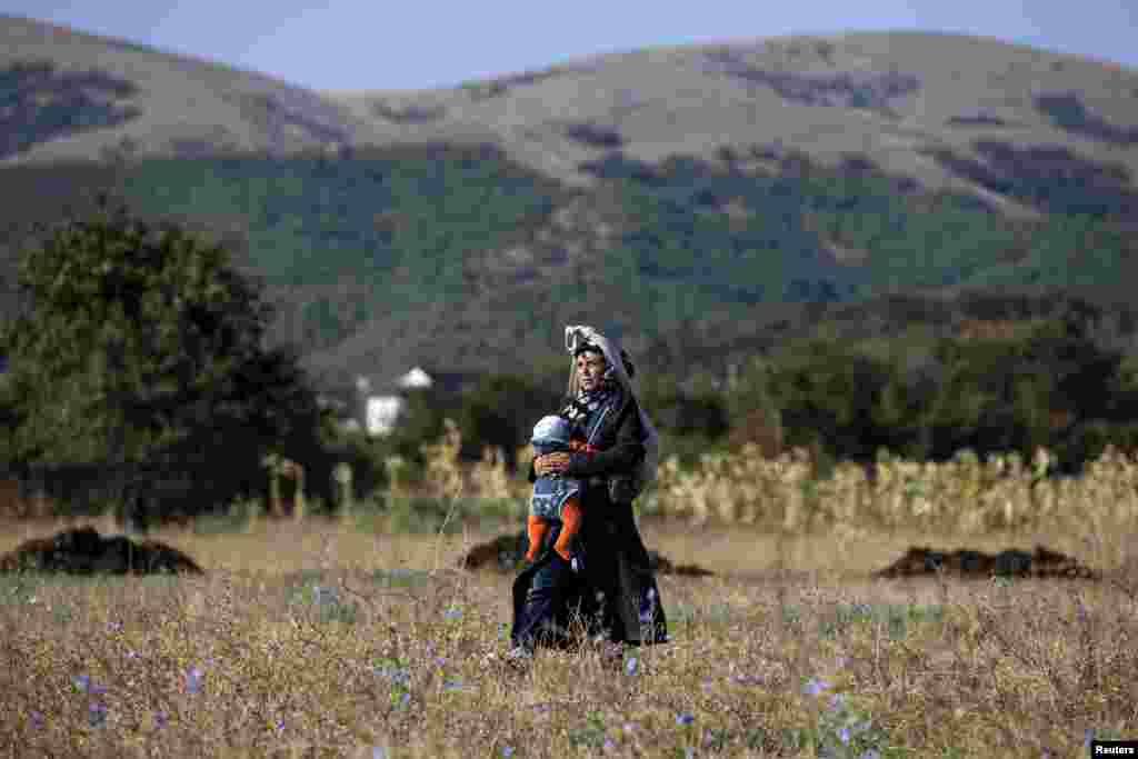 A migrant from Syria carries her child as she walks through a field in the village of Miratovac near the Serbian town of Presevo. Long lines of migrants, many of them refugees from Syria, snaked through southern Serbia by foot before jumping on trains and buses north to Hungary on the last leg of an increasingly desperate journey to Western Europe. (Reuters/Marko Djurica)