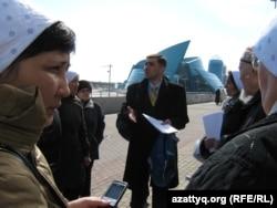 Правозащитник Вадим Курамшин стоит в окружении родственников осужденных, которые пытаются попасть в администрацию президента Казахстана с жалобами на пытки в тюрьмах. Астана, 1 апреля 2011 года.