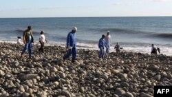 Волонтеры ищут обломки самолета на берегу острова Реюньон. 31 июля 2015 года.