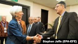 FILE: International Monetary Fund Managing Director Christine Lagarde (L) greets former Pakistani Finance Minister Asad Umar at the Bali Convention Centre during the 2018 IMF/World Bank Annual Meetings.