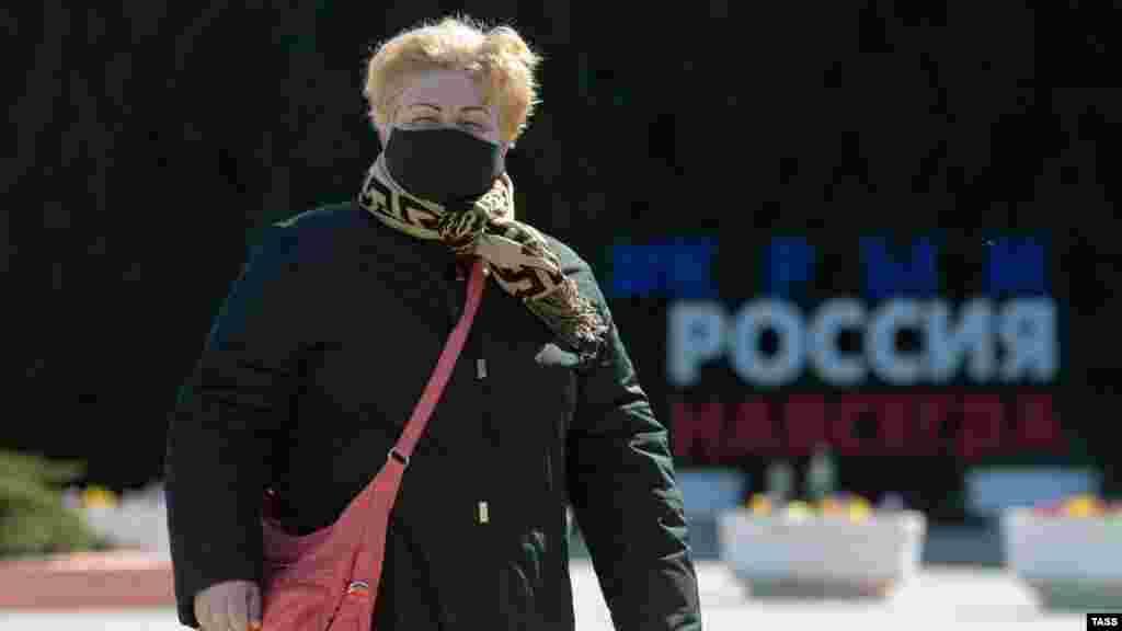 Женщина в защитной маске на площади Ленина в Симферополе