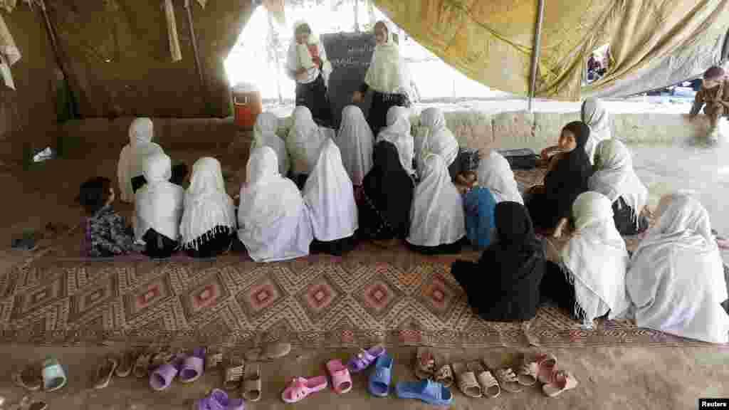 Female students attend classes in a tent in Jalalabad, Afghanistan.