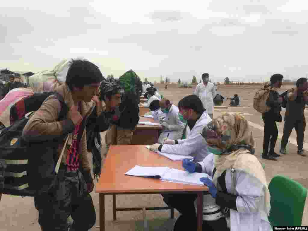 کارکنان صحی در مرز اسلام قلعه در جریان ثبت نام افغانهایی که از ایران برگشته اند.