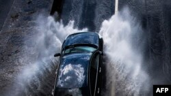 A car passes through a puddle following heavy rains in Moscow on July 21. (AFP/Mladen Antonov)