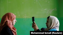 Alegătoare si funcționară electorală folosind un dispozitiv biometric in alegerile prezidențiale din Afganistan.