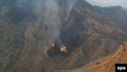 Пламя и дым на месте крушения пассажирского самолета в Пакистане. 7 декабря 2016 года.