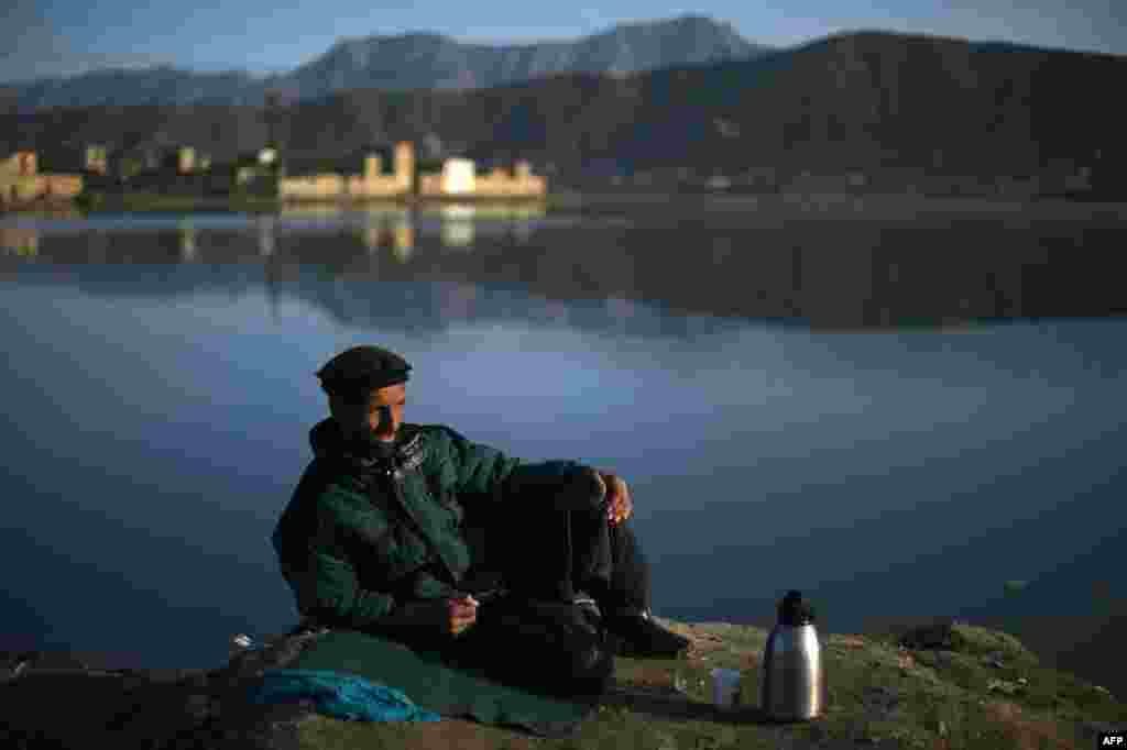 An Afghan car-wash worker waits for customers beside Shuhada Lake in Kabul. (AFP/Wakil Kohsar)