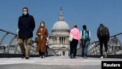 Люди в масках на Мосту тисячоліття в Лондоні під час кризи з коронавірусом