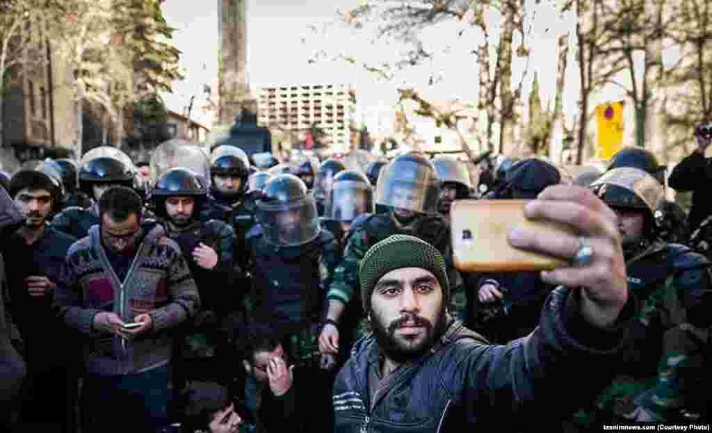 سلفی با نیروهای امنیتی در جریان حمله و اعتراض به سفارت عربستان در تهران.