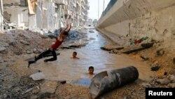 Алеппо қаласында лай суға түсіп жүрген балалар. Сирия, 10 шілде 2014 жыл.