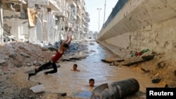 Купающиеся в яме, наполненной водой, дети в сирийском Алеппо, 10 июля 2014 года.