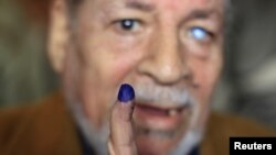 A man shows his ink-stained finger after casting his vote at a polling station in Cairo.