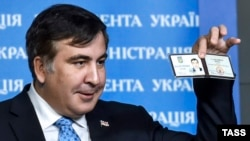 Former Georgian President Mikheil Saakashvili shows off his identification card as the head of an advisory council in Kyiv in February.