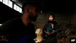 In this July 26, 2018 photo, Afghan musicians Hakim Ebrahimi, left, and Soraya Hosseini, members of the Arikayn rock band, play music at a furniture workshop on the outskirts of Tehran, Iran. Like others in Iran's vibrant arts scene, Afghan musicians must