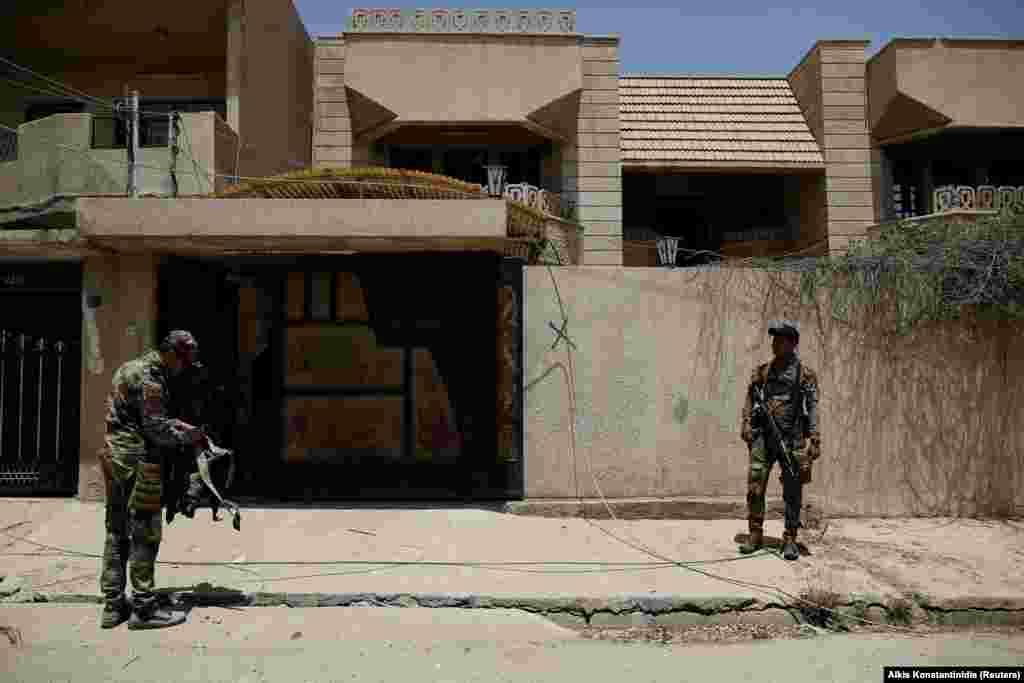Иракские военные за пределами виллы, которая использовалась в качестве тюрьмы боевиками «Исламского государства» (ИГ). Тайная тюрьма - пример новой тактики экстремистской группы, маскирующей свою деятельность в районах с гражданским населением.