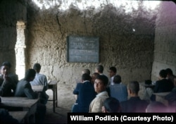 Afghan students learn chemistry in a mud-walled classroom.