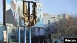 Президент Нұрсұлтан Назарбаевтың суреті салынған банерден қалғаны. Жаңаөзен қаласы, Маңғыстау облысы, 19 желтоқсан 2011 ж.