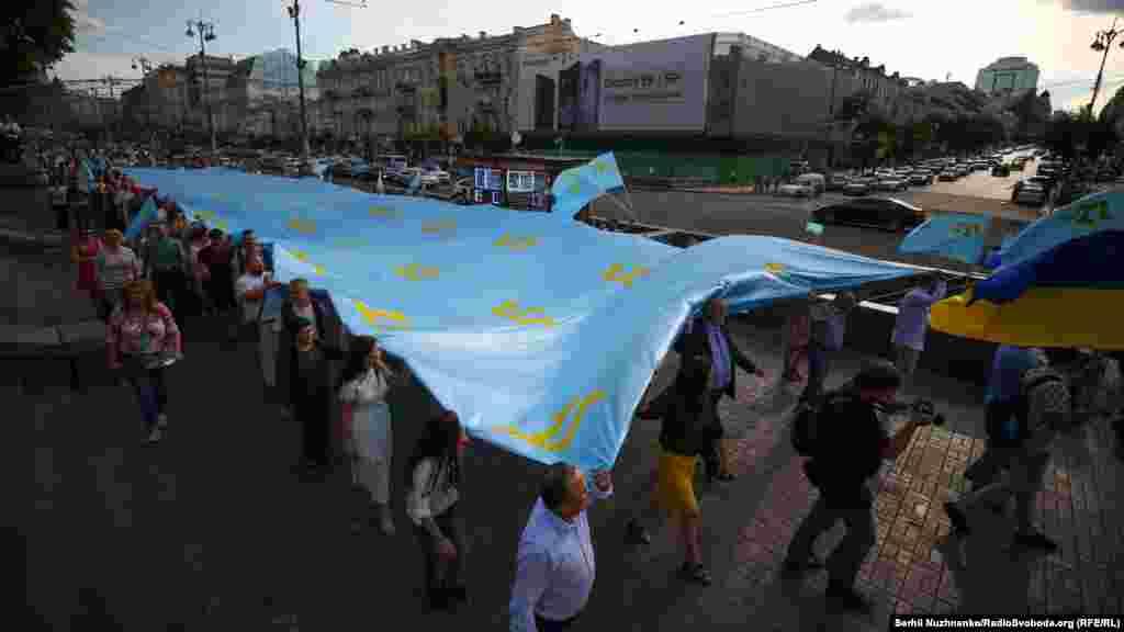 Люди йдуть Хрещатиком з національним прапором кримських татар під час мітингу з нагоди Дня кримськотатарського прапора, Київ, 26 червня 2018 року