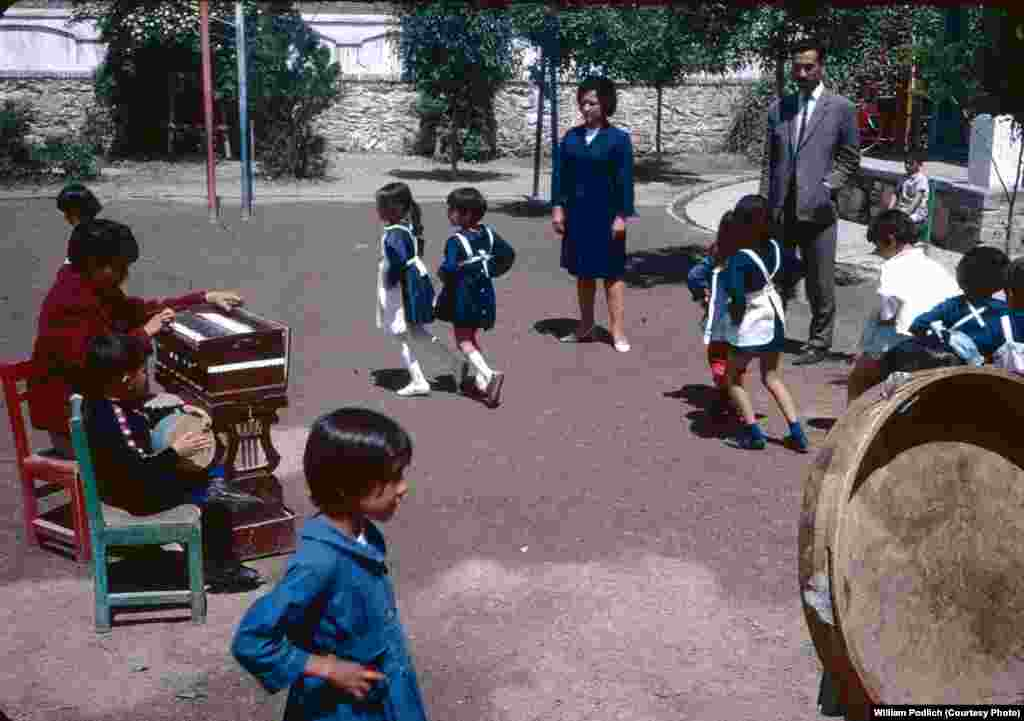 Young Afghan students dance on a school playground as a teacher and a student accompany on instruments.