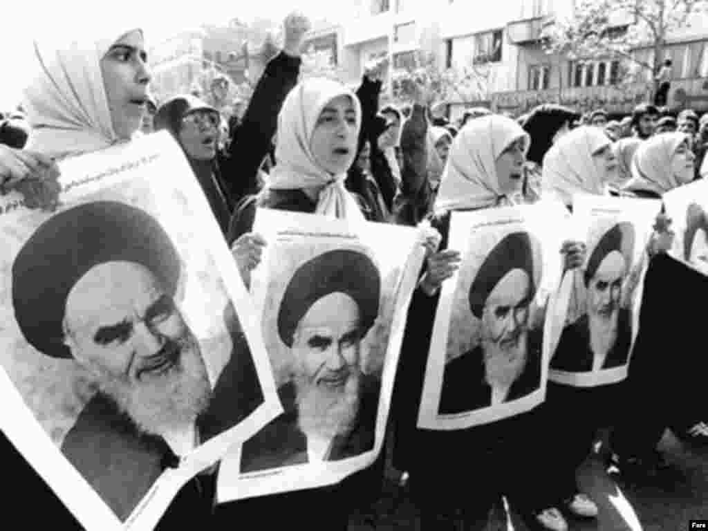 Women hold portraits of Khomeini in 1979.