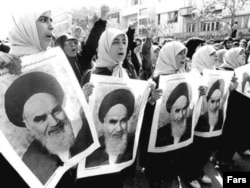 Iran – Girls supporters hold portraits of the religious leader of the revolution, Ayatollah Ruhollah Khomeini. 1979.