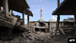 Damaged buildings and a minaret in the central Syrian town of Talbisah in Homs Province on September 30.