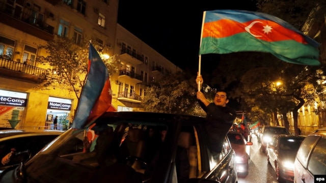 Supporters of Azerbaijani President Ilham Aliyev celebrate in the capital, Baku, after polls closed on October 9.