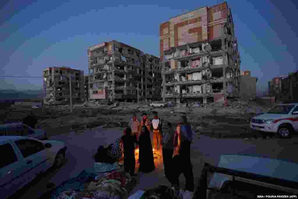 Residents huddle by a fire in an open area in Sarpol-e Zahab.