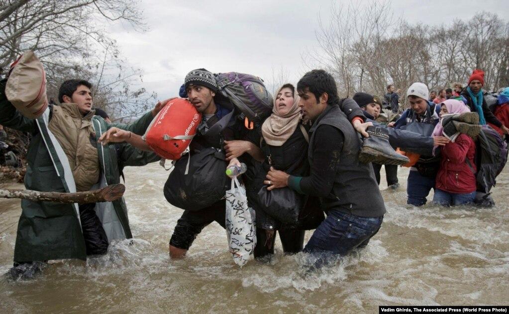Një grua ndihmohet nga dy burra për të kaluar lumin. Këta refugjatë kanë përdorur rrugë alternative për të hyrë në Maqedoni.
