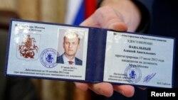 Керівник виборчкому Валентин Горбунов демонструє посвідчення кандидата на мера Москви Олексія Навального, 17 липня 2013 року
