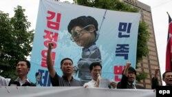 Сеул протестует против против действий северокорейского лидера Ким Чен Ира (карикатурно изображен на плакате).