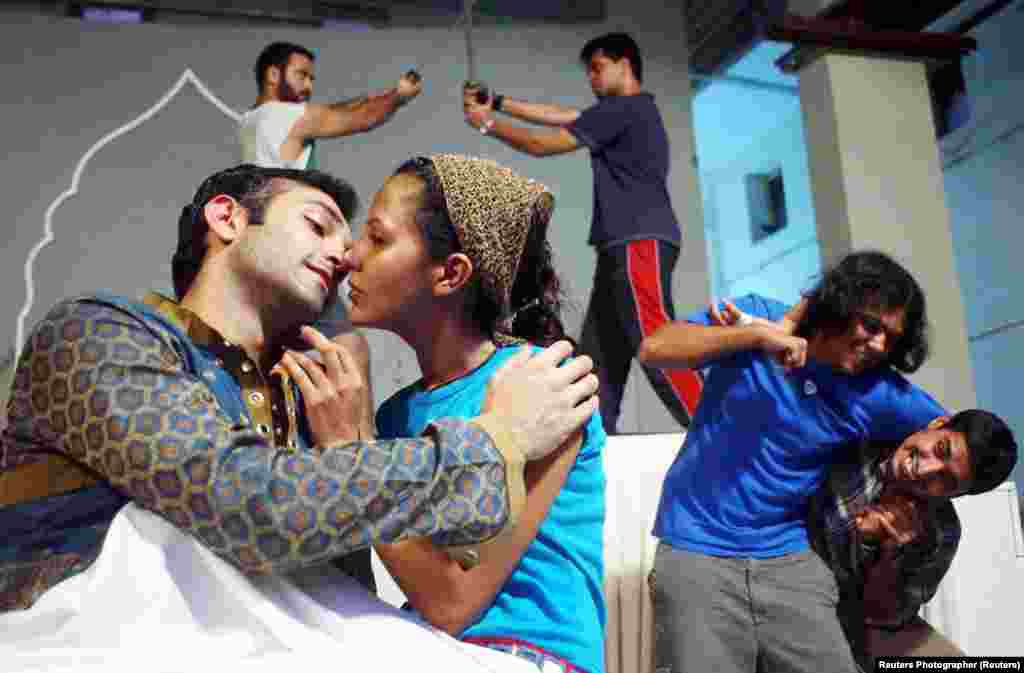 Actors play the roles of star-crossed lovers Romeo and Juliet as other performances stage-fight during a rehearsal in Mumbai. In this staging of the play, the director made the leading roles a Muslim Romeo and a Hindu Juliet.