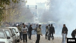 Protesters and Iranian students face off against riot police in Tehran on December 8.