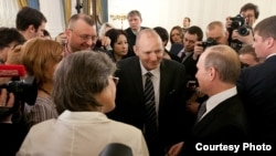 Andrei Stolbunov (wearing glasses) stands next to journalist and environmental activist Mikhail Beketov (center, wearing suit) opposite Russian leader Vladimir Putin at a reception in 2012.