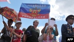"Children hold a flag of the self-styled ""People's Republic of Luhansk"" during a rally in the eastern Ukrainian city of Luhansk in June."