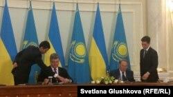 Президент Казахстана Нурсултан Назарбаев (сидит справа) и президент Украины Петр Порошенко подписывают документы после переговоров. Астана, 9 октября 2015 года.