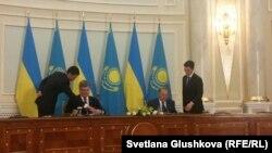 Қазақстан президенті Нұрсұлтан Назарбаев (оң жақта) пен Украина президенті Петр Порошенко келіссөздерден соң құжаттарға қол қойып отыр. Астана, 9 қазан 2015 жыл.