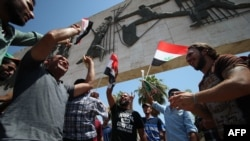 Iraqi demonstrators gather in the streets of Baghdad on August 14, shouting slogans in support of reforms proposed by Iraqi Prime Minister Haidar al-Abadi aimed at curbing corruption.