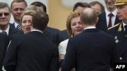 Orsýetiň prezidenti Wladimir Putin (sagda) ýan ýoldaşy Lýudmilany ogşaýar, öňki prezident Dmitriý Medwedew bolsa aýaly Swetlanany ogşaýar, Kreml, 7-nji maý.