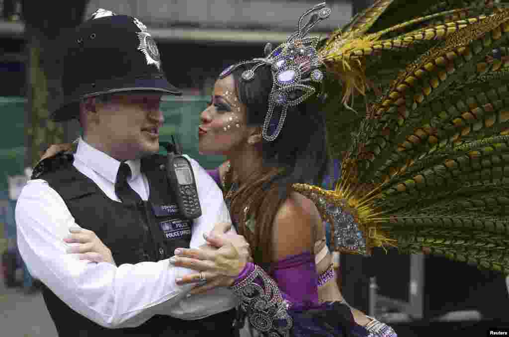 A street performer tries to dance with a police officer during the Notting Hill Carnival in London. (Reuters/Neil Hall)